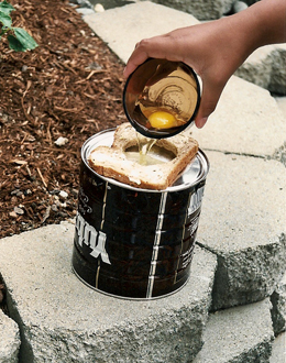 1) Butter a piece of bread on both sides.  2) Cut a circle from the center of the bread slice, using a cookie cutter or the top of another can.  3) Place the buttered bread on the hot hobo stovetop, break an egg into the hole, and sprinkle with salt and pepper to taste.